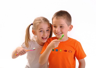 Two children brush their teeth isolated on white